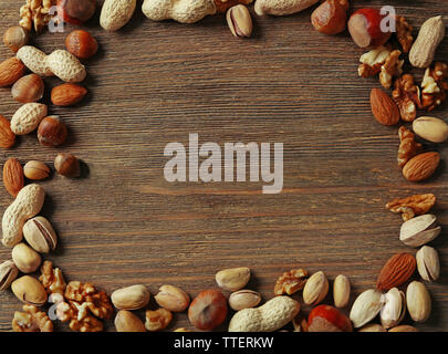 Frame made with mix of nuts on the wooden table - Stock Photo