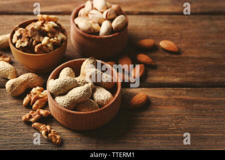 Pistachios, almonds, peanuts and walnut kernels in the wooden bowls on the table - Stock Photo