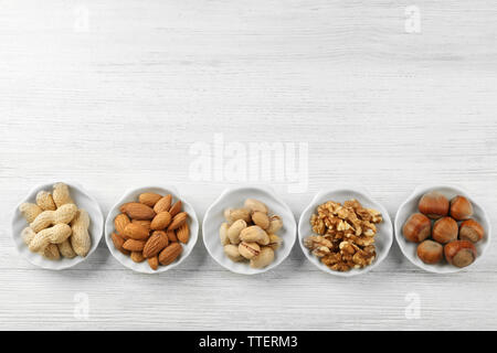 Pistachios, almonds, peanuts, walnut kernels and hazelnuts in the bowls on white wooden table - Stock Photo