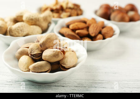 Pistachios, almonds, peanuts, walnut kernels and hazelnuts in the bowls on white wooden table, close-up - Stock Photo