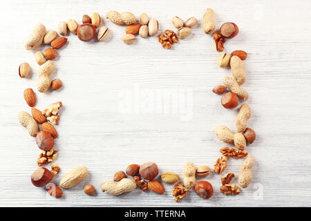 Frame made with mix of nuts on the white wooden table - Stock Photo