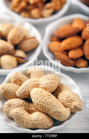 Peanuts, pistachios, almonds and walnut kernels in the bowls, close-up - Stock Photo