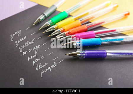 Set of colored pens on black paper - Stock Photo