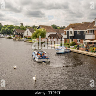 Two small day boats on hire and heading out of Wroxham and up the River Bure - Stock Photo