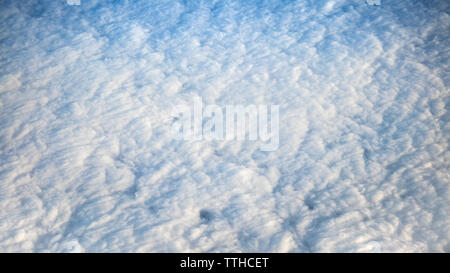 Wonderful view of cloudscape with clear blue sky from above. Beautiful panorama above white clouds as seen through window of an aircraft. - Stock Photo