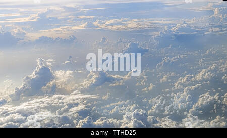 Wonderful view of the sky and clouds with the light the sun from above, as seen through airplane window. Beautiful view of passenger traveling by air. - Stock Photo