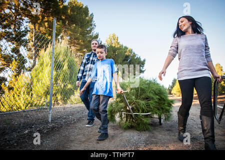 Boy pulling cart while walking with parents on road - Stock Photo