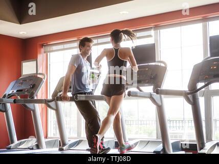 Happy man looking at woman running on treadmill at gym - Stock Photo
