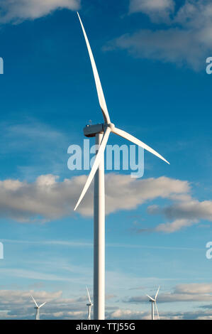 Wind turbines against sky on sunny day - Stock Photo
