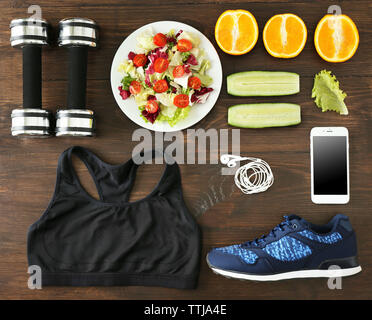 Sport equipment and healthy food on wooden background - Stock Photo