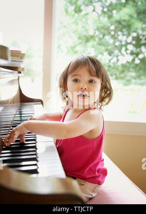 Curious baby girl looking away while playing with piano - Stock Photo