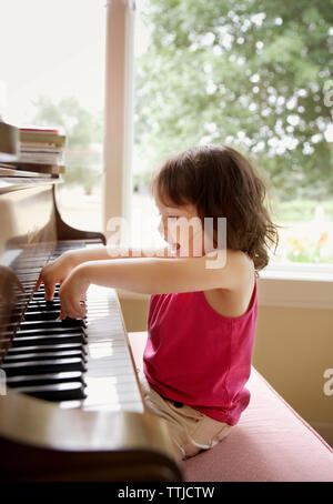 Happy baby girl playing with piano at home - Stock Photo