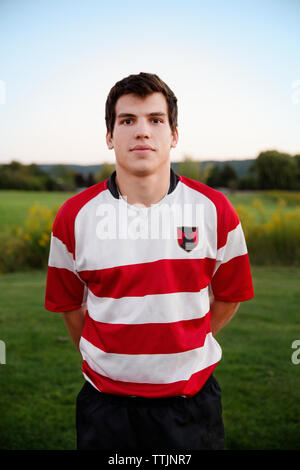 Portrait of confident rugby player standing with hands behind back on field - Stock Photo