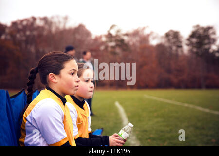 Friends wearing sports uniform resting on chair at soccer field - Stock Photo