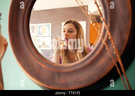 Woman applying lipstick while looking in mirror at home - Stock Photo