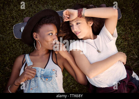 Overhead view of friends resting head on skateboard while lying on grassy field - Stock Photo