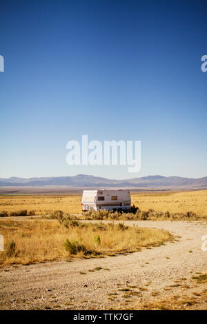 Camper van parked on field against clear sky - Stock Photo