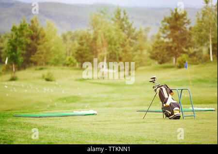 Golf clubs in bag on field - Stock Photo