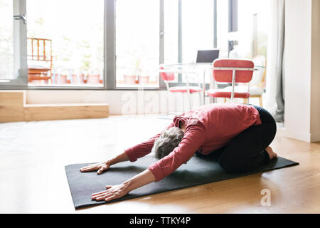 Mature woman practicing yoga in child's pose at home - Stock Photo