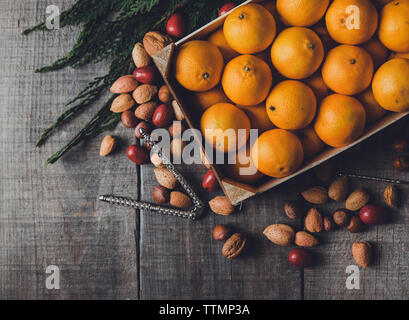 High angle view of oranges in box by various dry fruits and nutcracker on wooden table - Stock Photo
