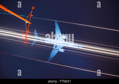Low angle view of signal mast against light trails and airplane in sky at night - Stock Photo