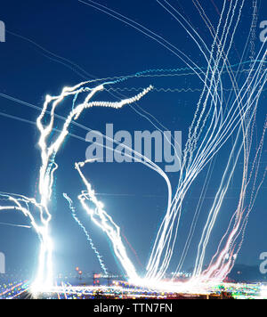 Low angle view of light paintings against blue sky at night - Stock Photo