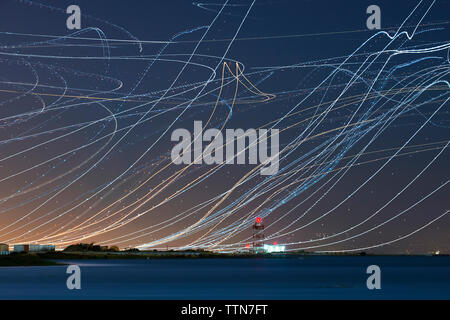 Low angle view of light paintings over river against sky at night - Stock Photo