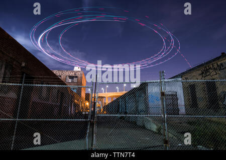 Low angle view of light paintings spinning over buildings at night - Stock Photo