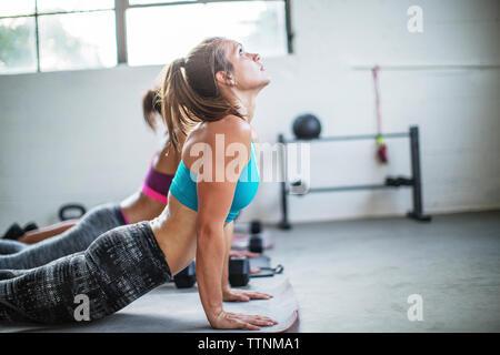 Female athletes practicing upward facing dog position in gym - Stock Photo
