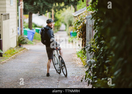 Portrait of smiling male commuter with bicycle standing on street - Stock Photo
