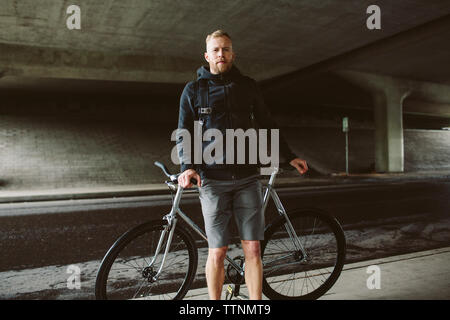 Portrait of confident male commuter standing by bicycle on bridge - Stock Photo