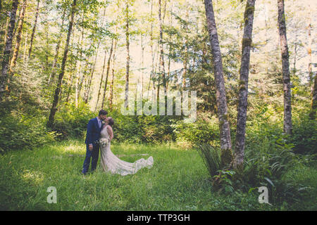 Newlywed couple kissing while standing on grassy field in forest - Stock Photo