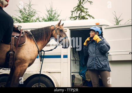 Female doctor wearing helmet while standing with horse against ambulance - Stock Photo
