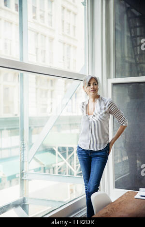 Thoughtful businesswoman standing by window in creative office - Stock Photo