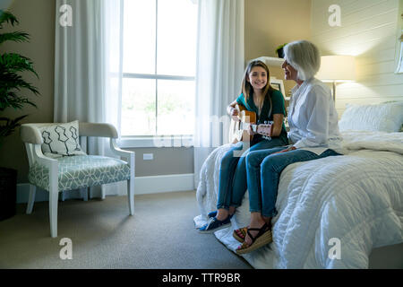 Granddaughter playing guitar while sitting by grandmother on bed - Stock Photo