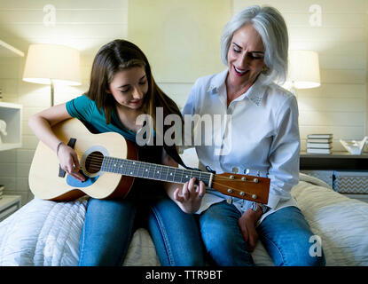 Grandmother looking at granddaughter playing guitar while sitting on bed - Stock Photo