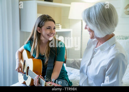 Happy granddaughter playing guitar while sitting by grandmother in bedroom - Stock Photo