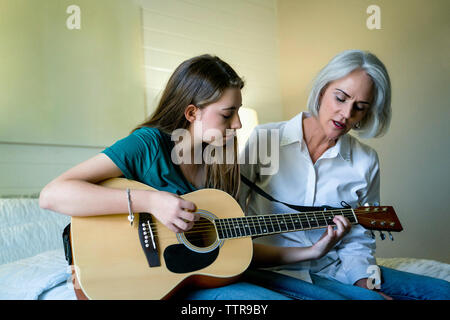 Granddaughter playing guitar while sitting by grandmother in bedroom - Stock Photo