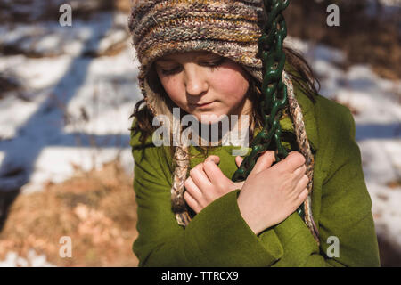 Close-up of sad girl sitting on swing at playground during winter - Stock Photo