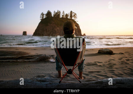 Rear view of teenage boy sitting on deck chair at beach during sunset - Stock Photo