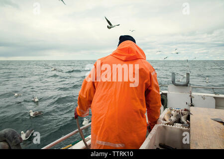 Rear view of fisherman standing on fishing boat at sea against cloudy sky - Stock Photo