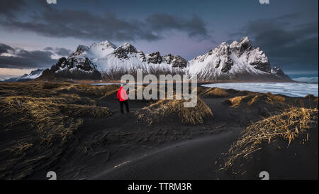 Back view of person on dark ground of wild lands near river and high rock hills in snow in Vestrahorn, Stokksnes, Iceland - Stock Photo