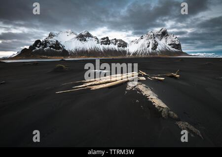 Dark soil of wild lands near water and amazing high rock hills in snow and cloudy sky in Vestrahorn, Stokksnes, Iceland - Stock Photo