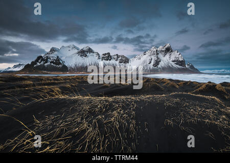 Dark ground of wild lands near river and amazing high rock hills in snow in Vestrahorn, Stokksnes, Iceland - Stock Photo