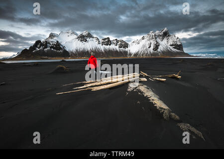 Back view of person on dark soil of wild lands near water and amazing high rock hills in snow and cloudy sky in Vestrahorn, Stokksnes, Iceland - Stock Photo