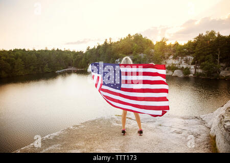Rear view of woman holding American flag on rock overlooking lake - Stock Photo