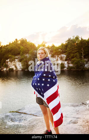 Portrait of woman wrapped in American flag standing on rock overlooking lake - Stock Photo
