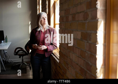 Thoughtful mature businesswoman looking through window while holding smart phone in creative office - Stock Photo