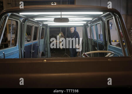 Engineer examining van in automobile factory seen through windshield - Stock Photo