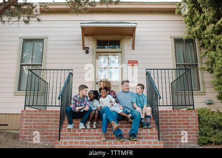 Full length of happy family at sitting on steps at entrance of building - Stock Photo